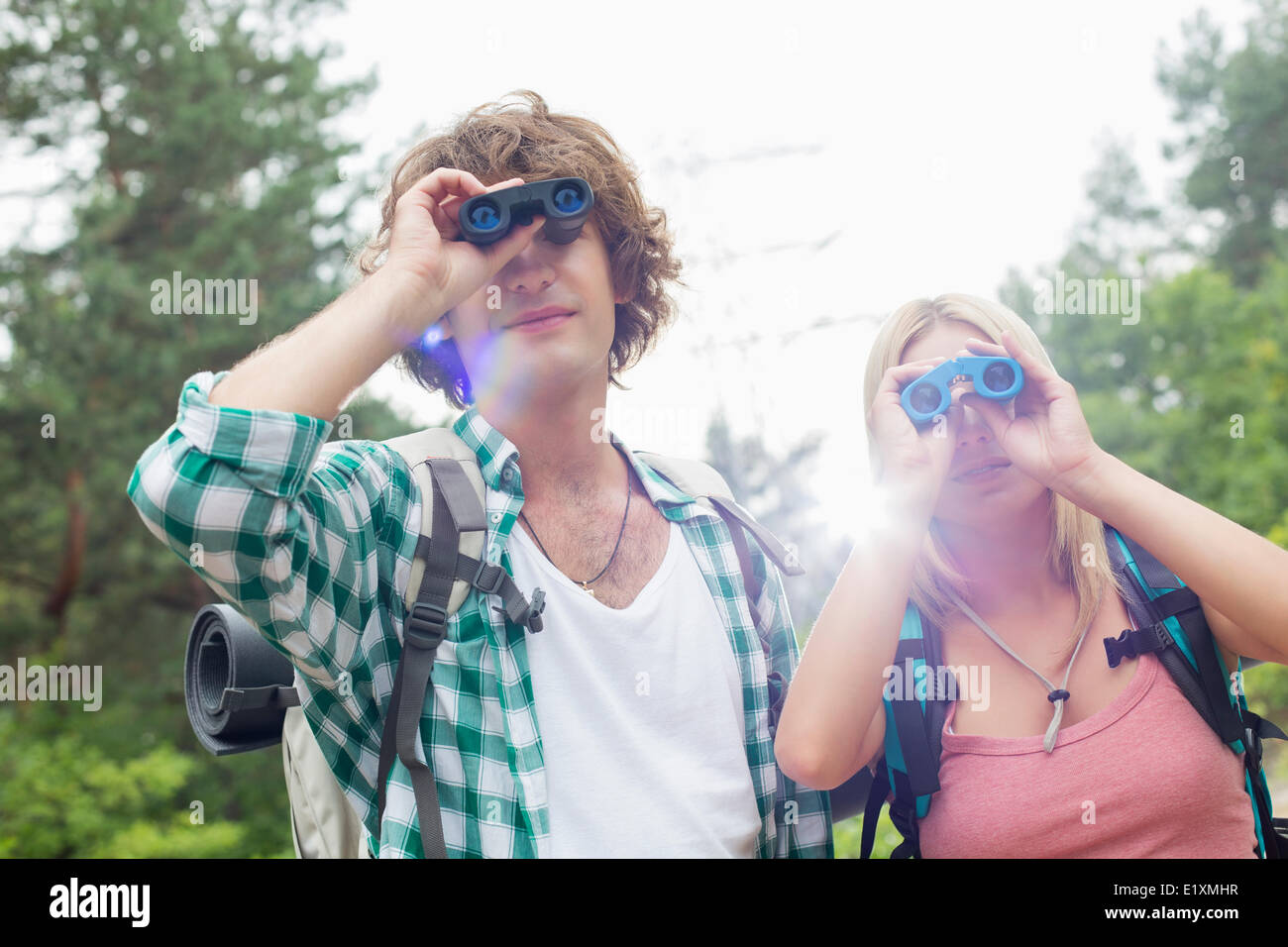 Young hiking couple using binoculars in forest - Stock Image