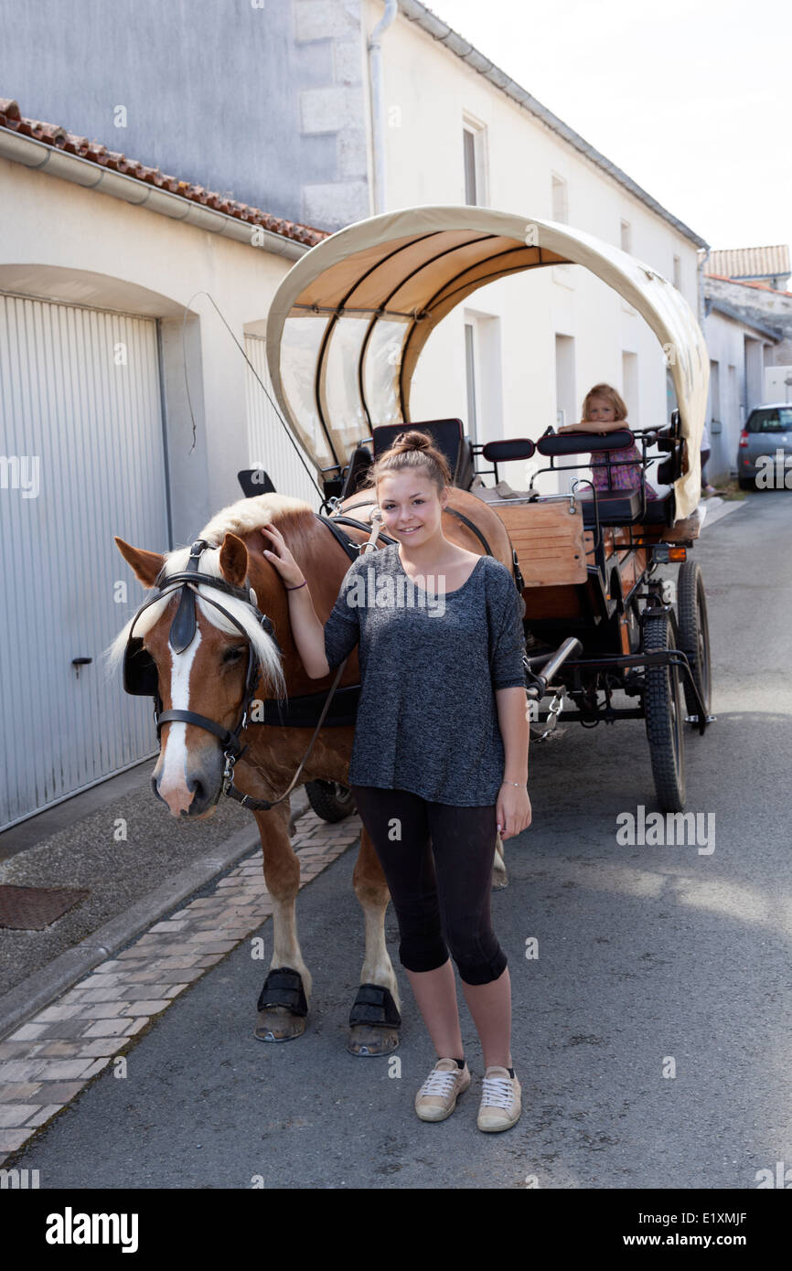 The good-looking girl with a horse-drawn cart (la Ronde - France). La belle jeune fille à l'attelage hippomobile - Stock Image