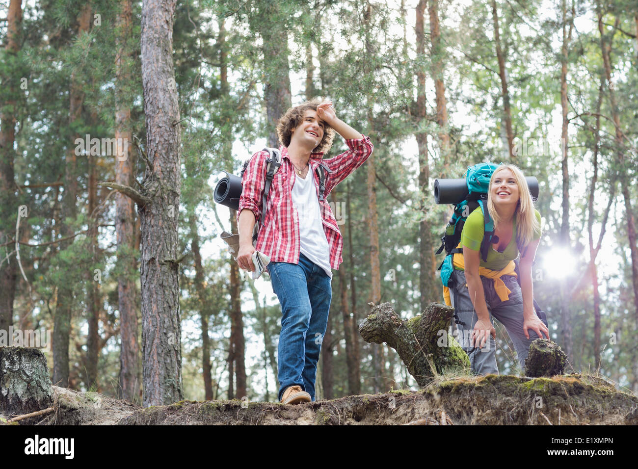 Tired young hiking couple taking a break in forest - Stock Image