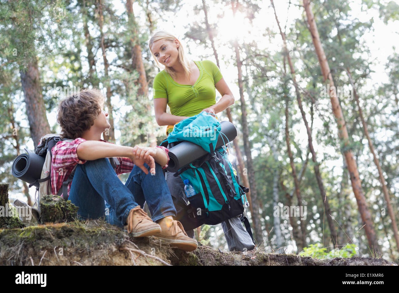 Young hiking couple looking at each other in forest - Stock Image