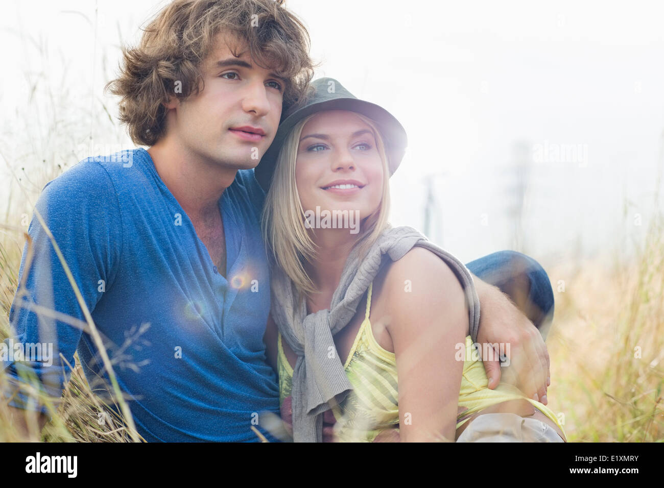 Romantic young couple looking away while sitting in field - Stock Image