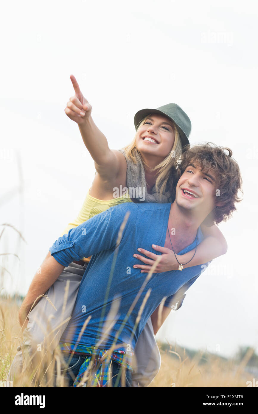 Cheerful woman showing something while enjoying piggyback ride on man in field - Stock Image