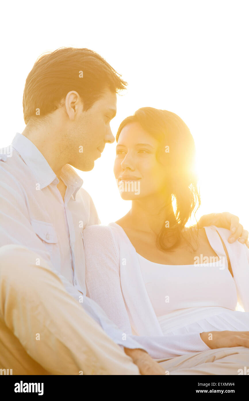 Loving young couple looking at each other against clear sky - Stock Image
