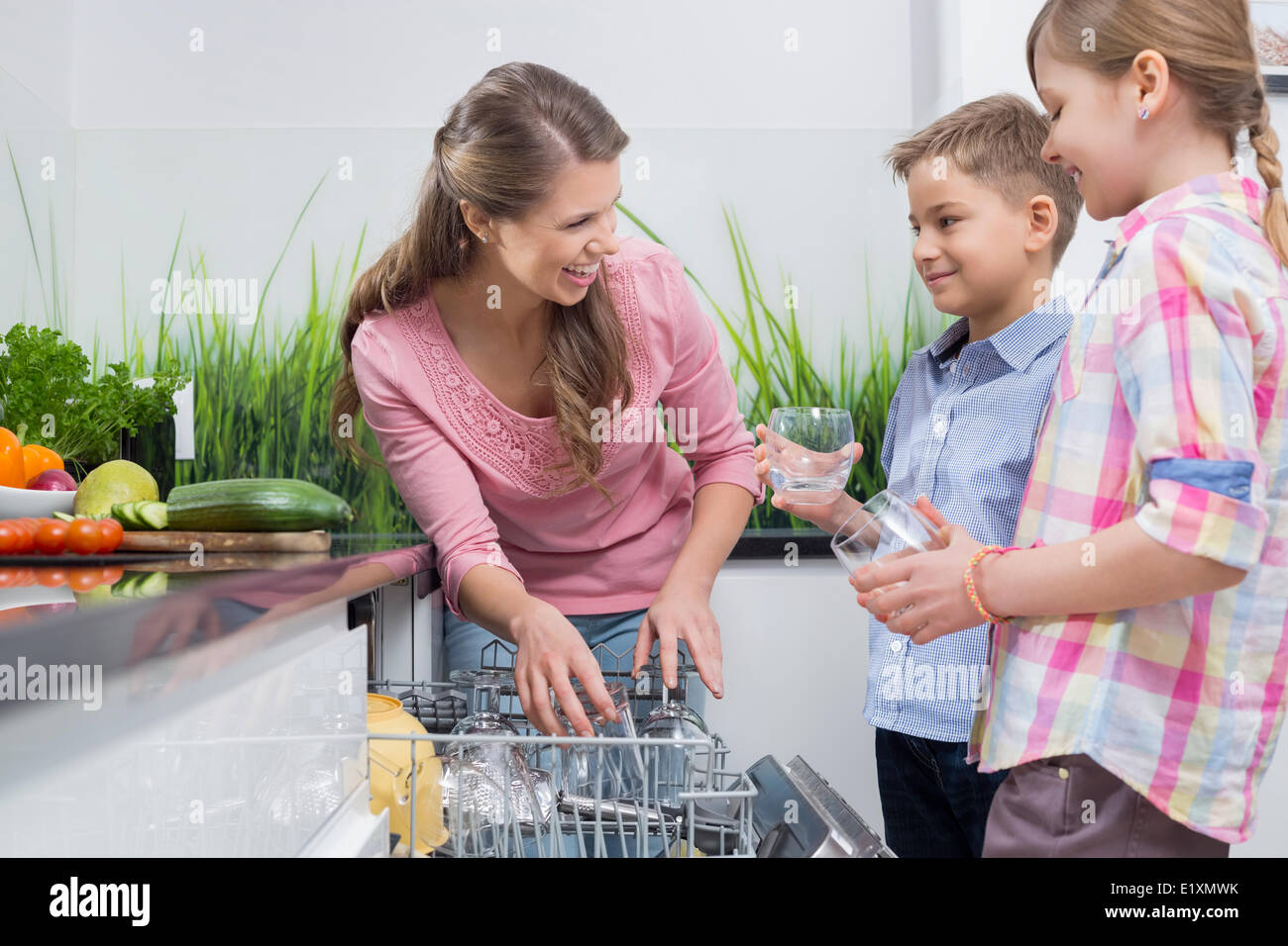 Happy mother and children placing glasses in dishwasher - Stock Image