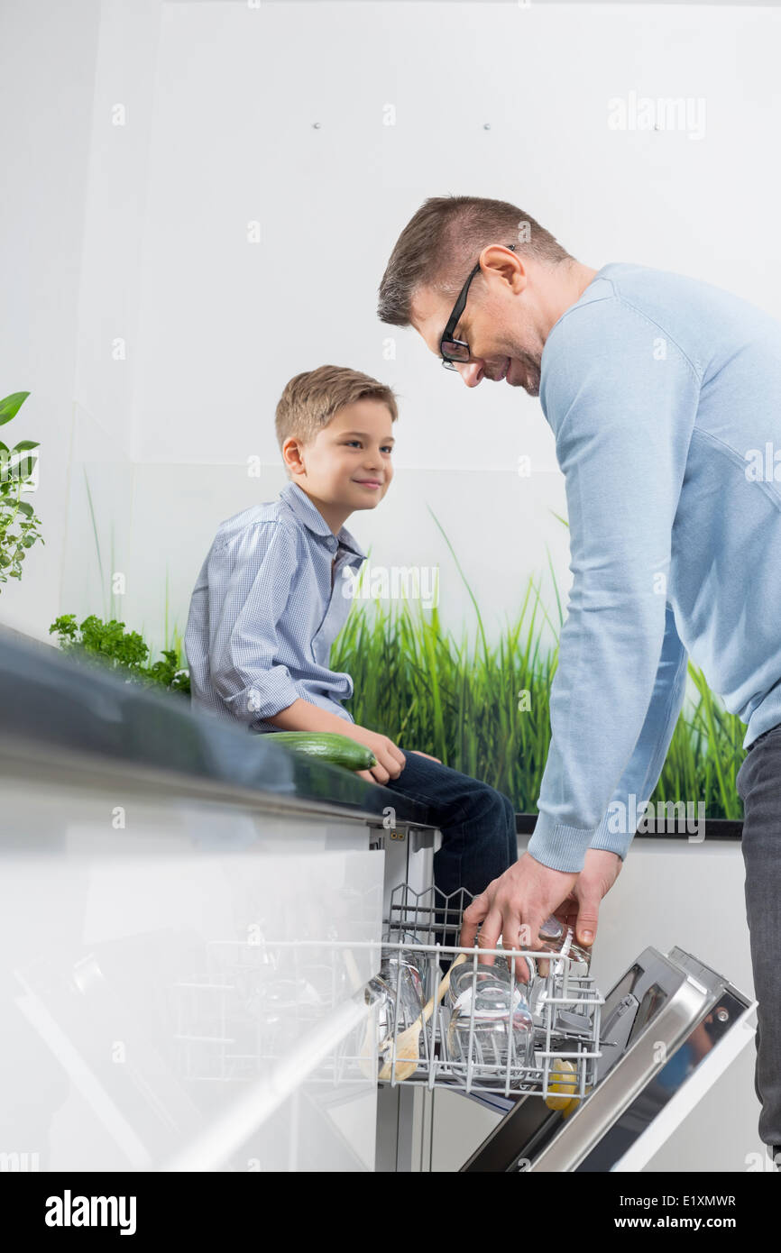 Boy looking at father placing glass in dishwasher at kitchen - Stock Image