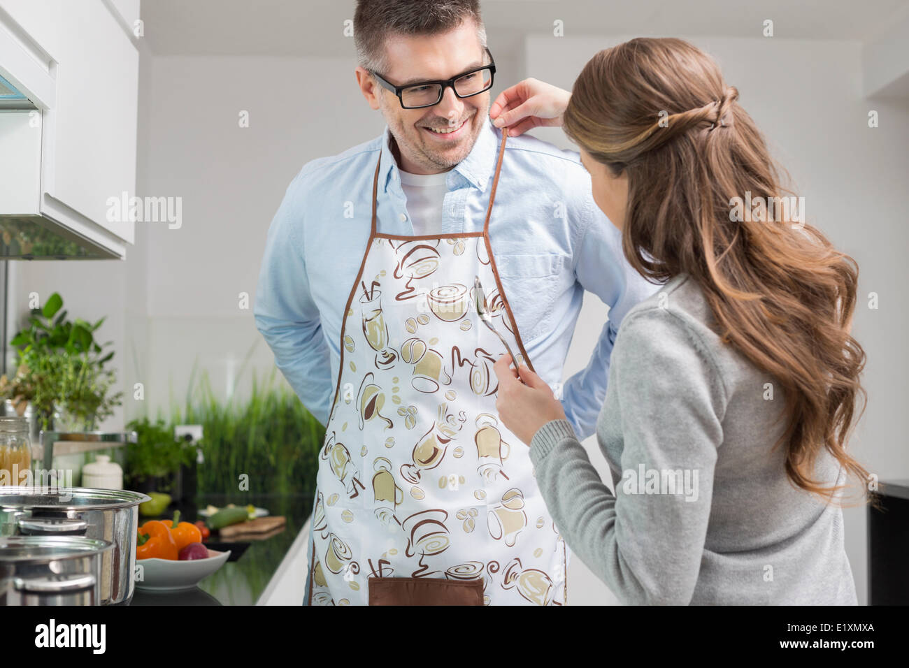 Woman helping man to put on apron in kitchen - Stock Image