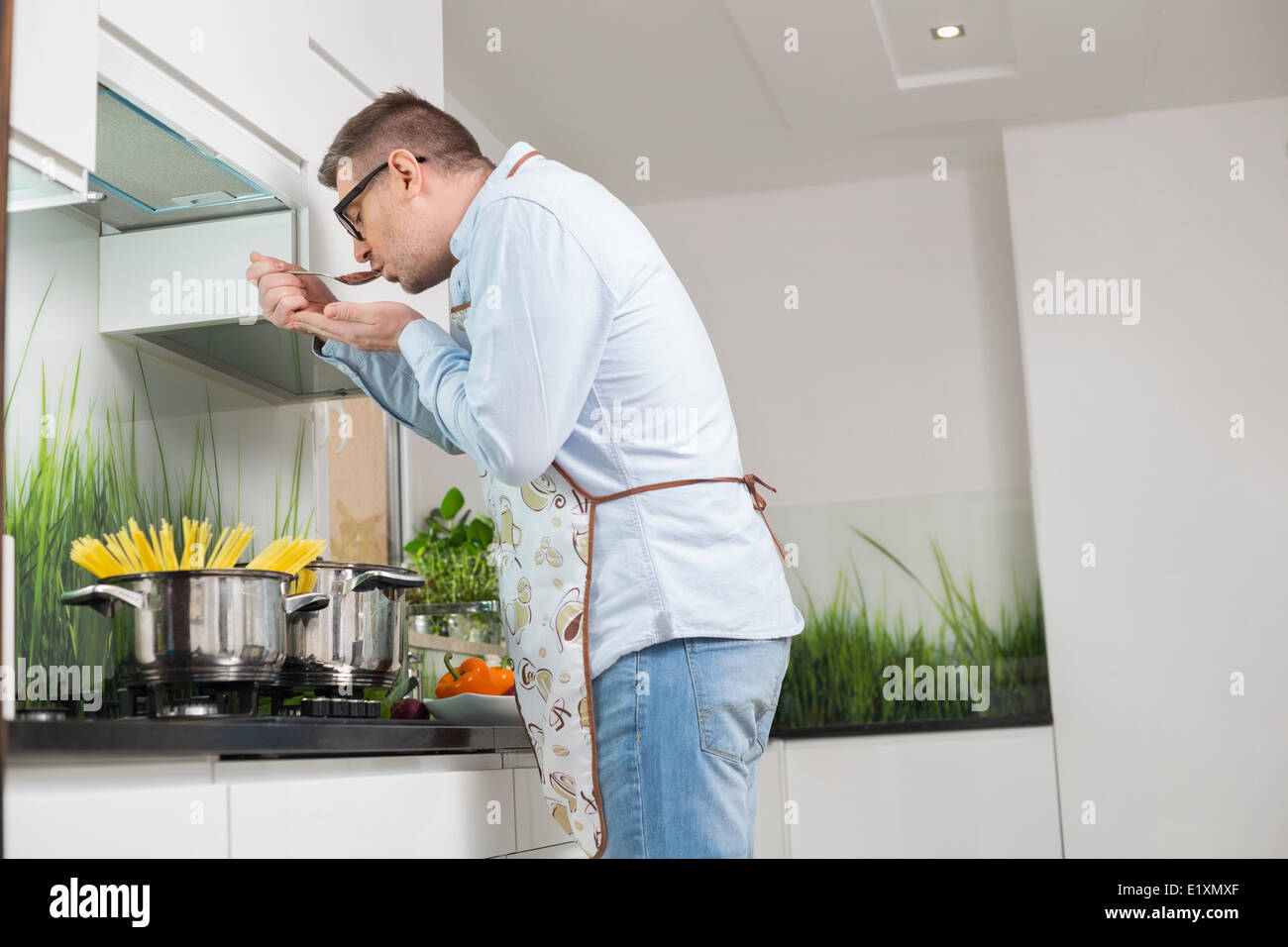 Side view of man tasting food while cooking in kitchen Stock Photo ...