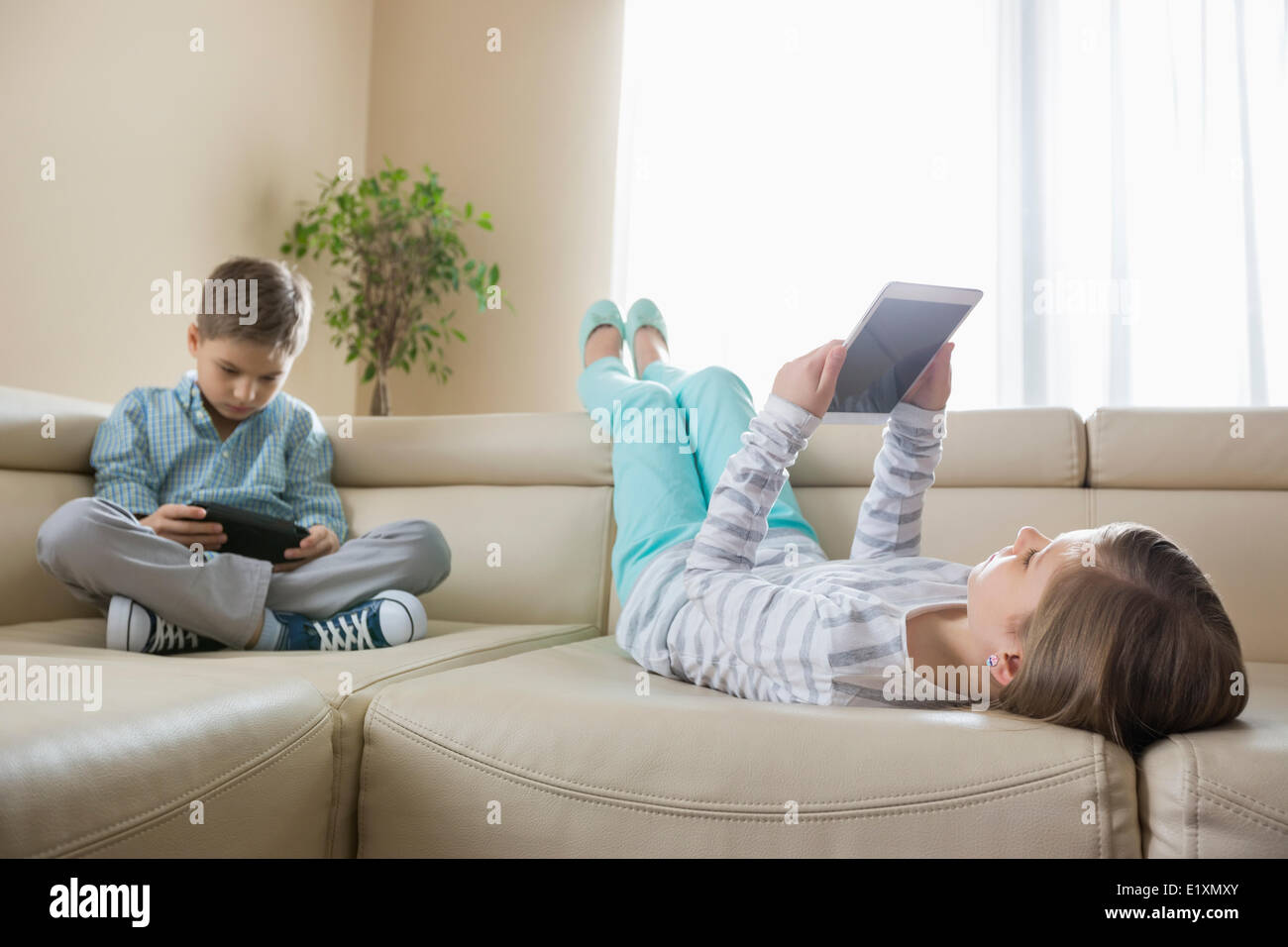 Siblings using technologies on sofa at home - Stock Image