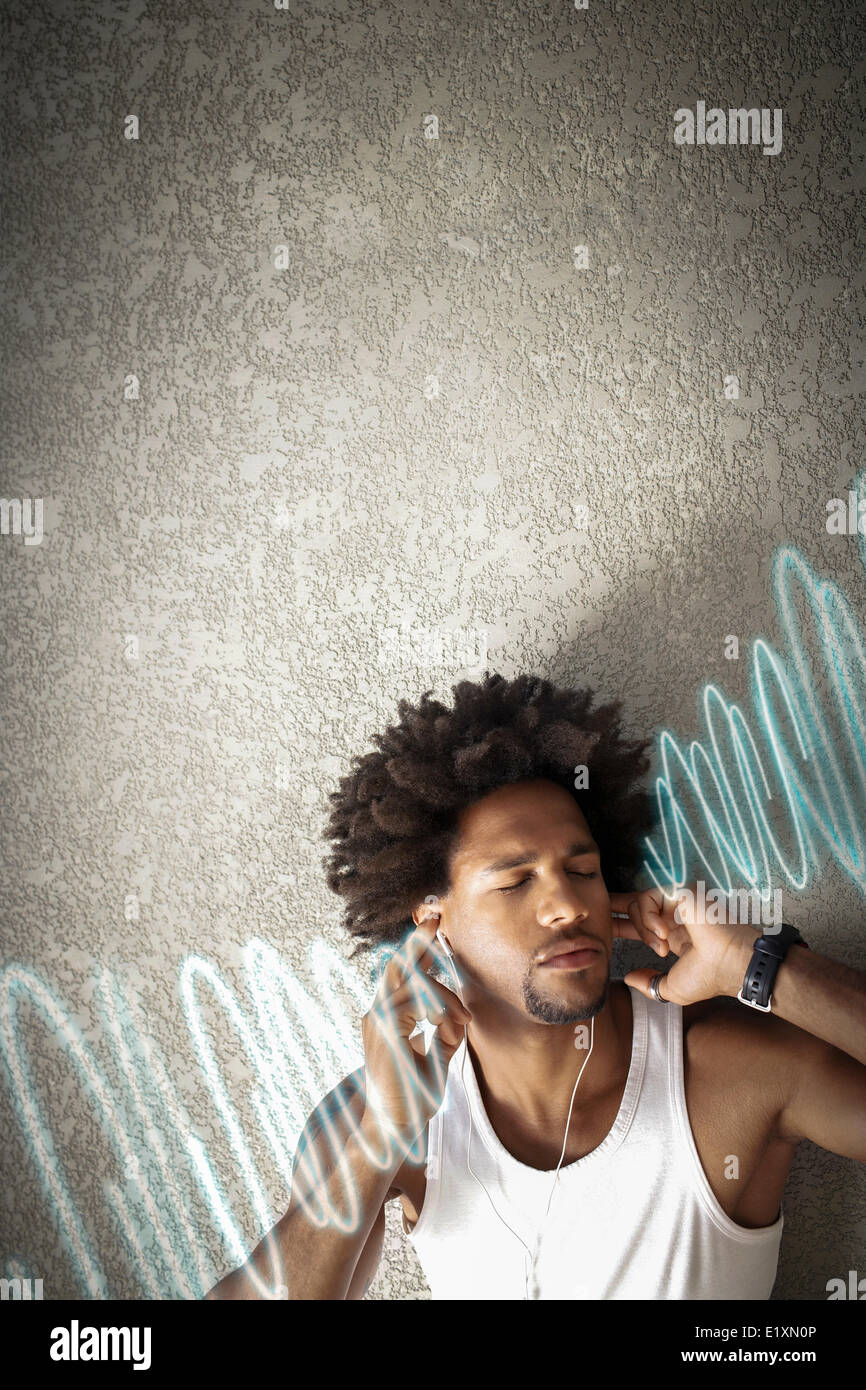 Relaxed young man listening music while leaning on wall - Stock Image