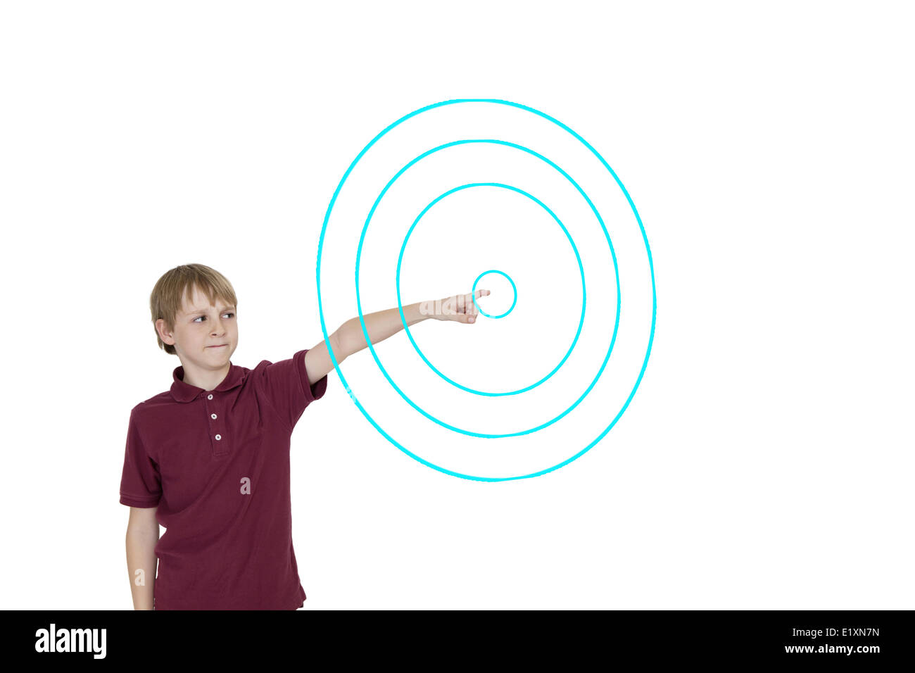 Young boy pointing to digitally designed concentric circles over white background - Stock Image
