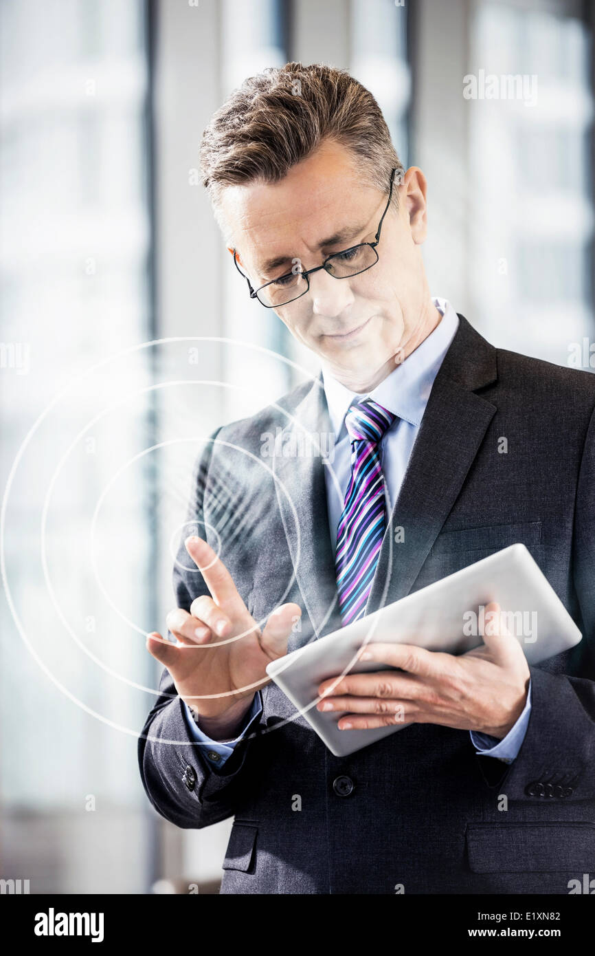 Middle aged businessman using digital tablet in office - Stock Image