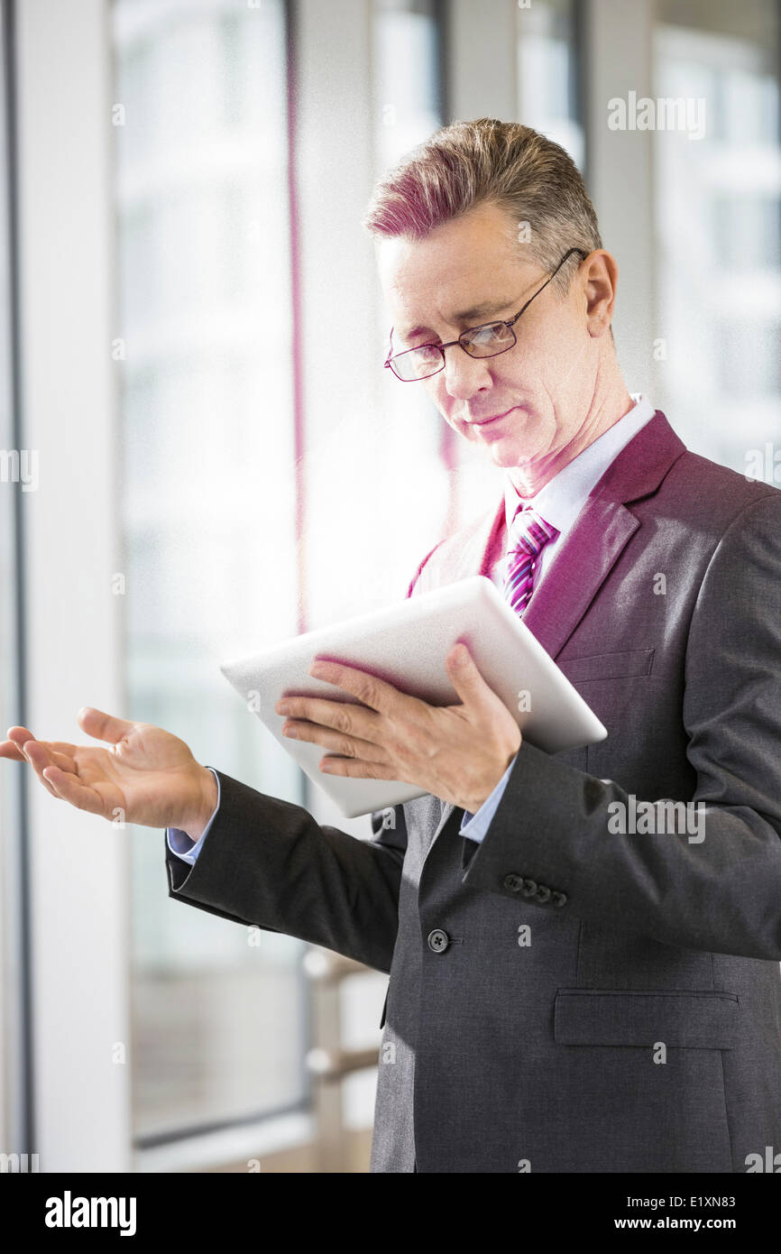 Middle aged businessman using tablet PC in office - Stock Image