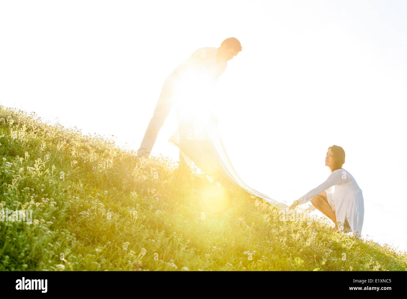 Tilt image of young couple spreading picnic blanket on grass during sunny day - Stock Image