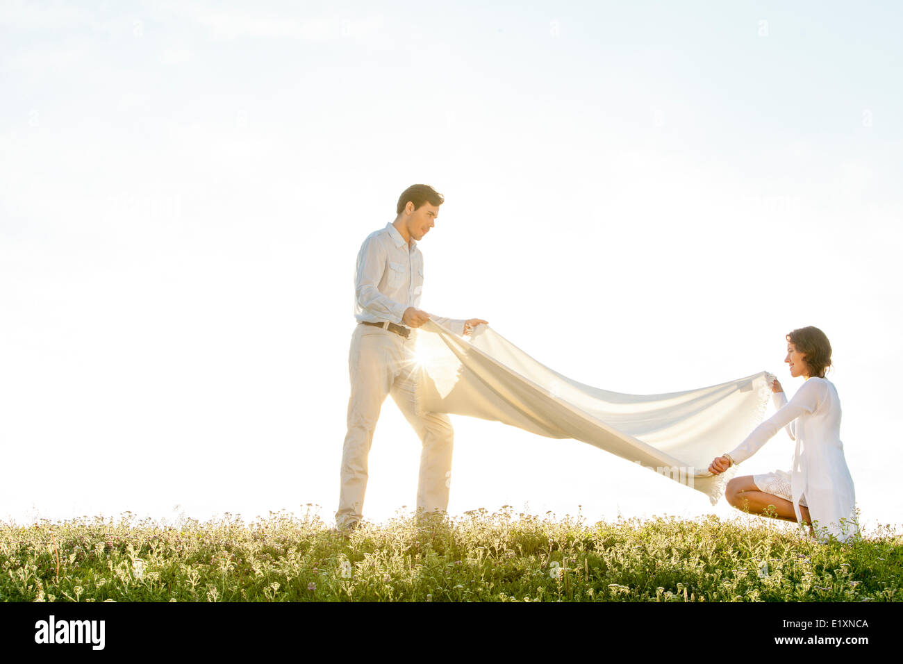 Side view of woman and man spreading picnic blanket on grass during sunny day - Stock Image