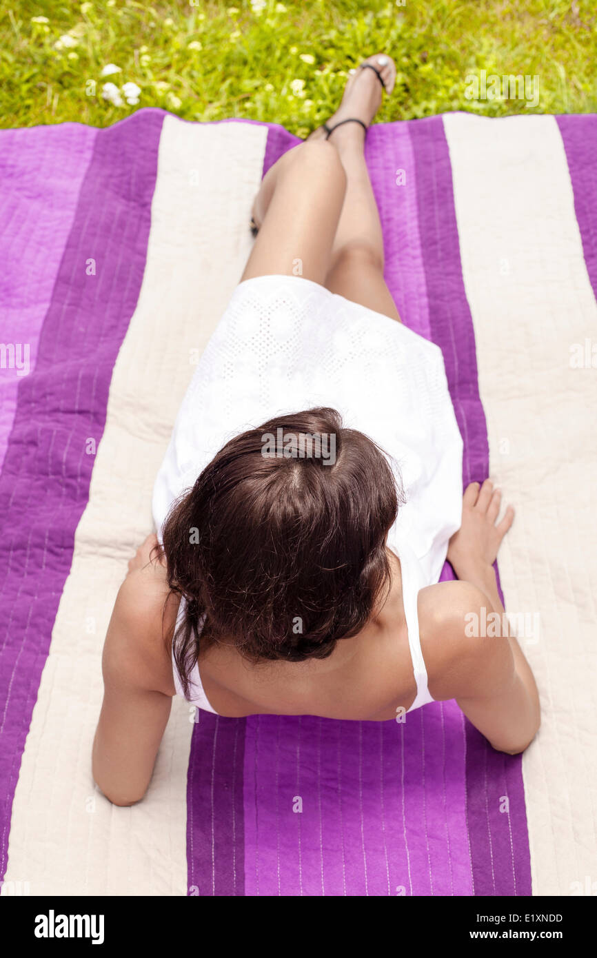 Young woman leaning on elbows while lying on picnic blanket in park - Stock Image