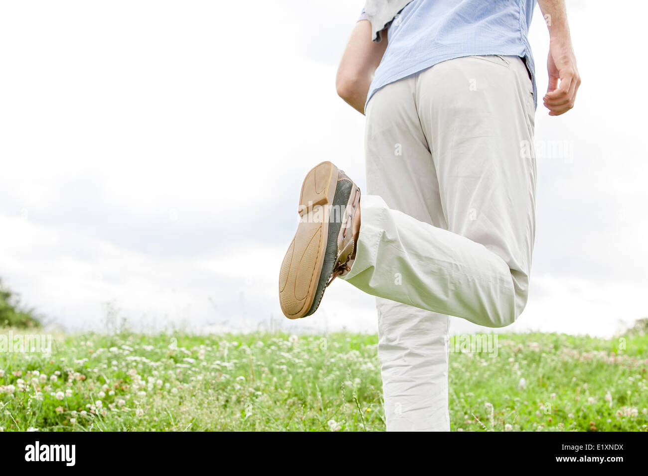 Cropped image of man running in park against sky - Stock Image