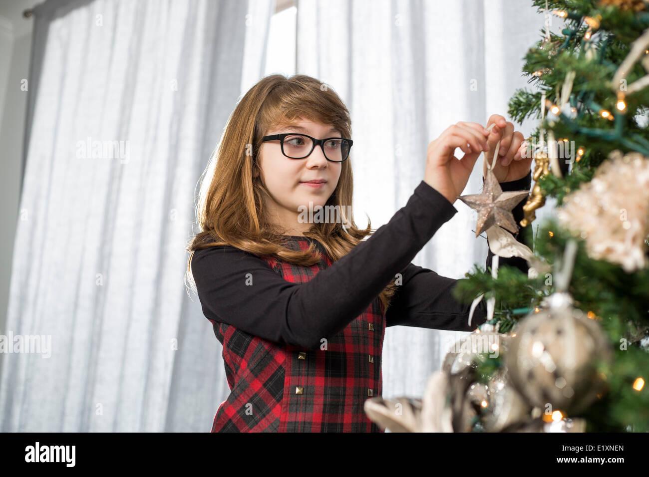 Teenage girl hanging ornament on Christmas tree at home - Stock Image