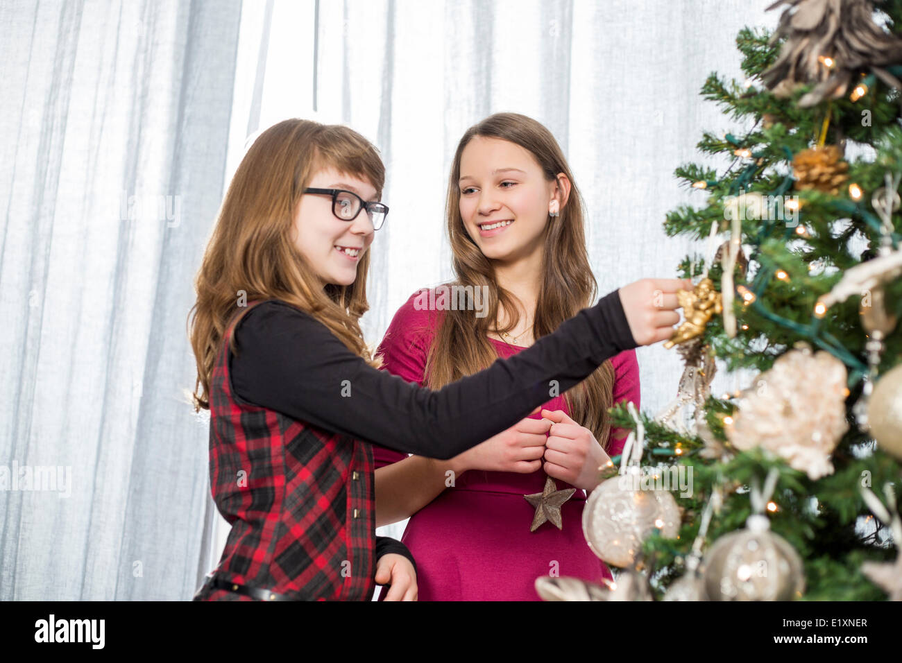 Sisters decorating on Christmas tree at home - Stock Image