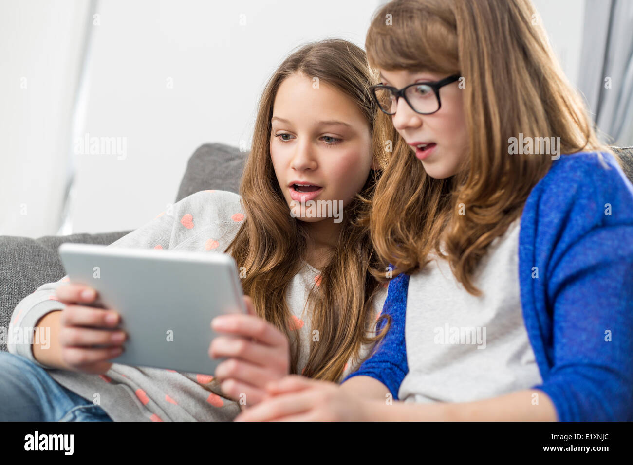Shocked sisters using digital tablet on sofa at home - Stock Image