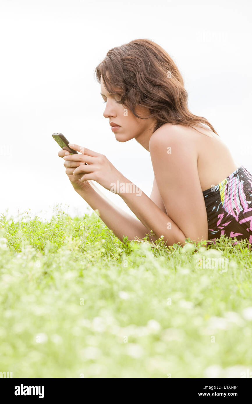 Side view of young woman text messaging through cell phone while lying on grass against clear sky - Stock Image