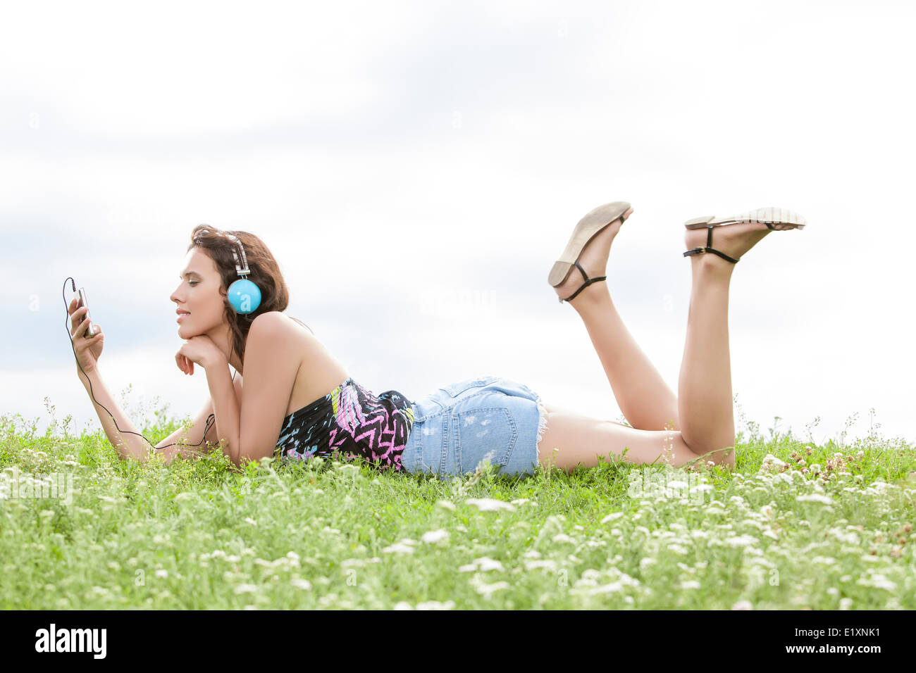 Profile shot of woman listening to music through cell phone using headphones while lying on grass against sky - Stock Image