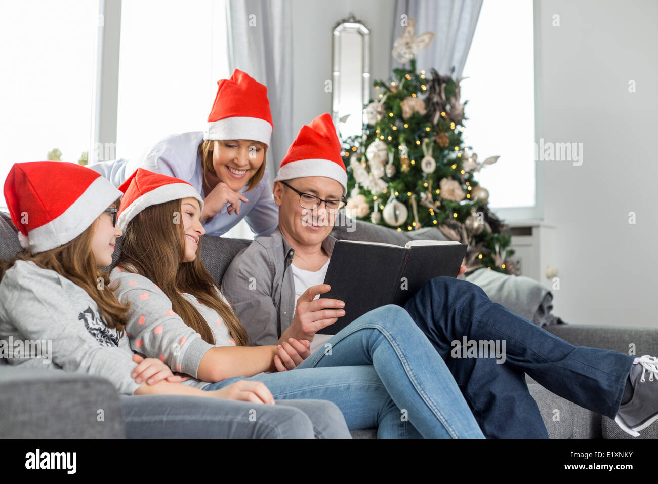 Family of four reading book in living room during Christmas - Stock Image