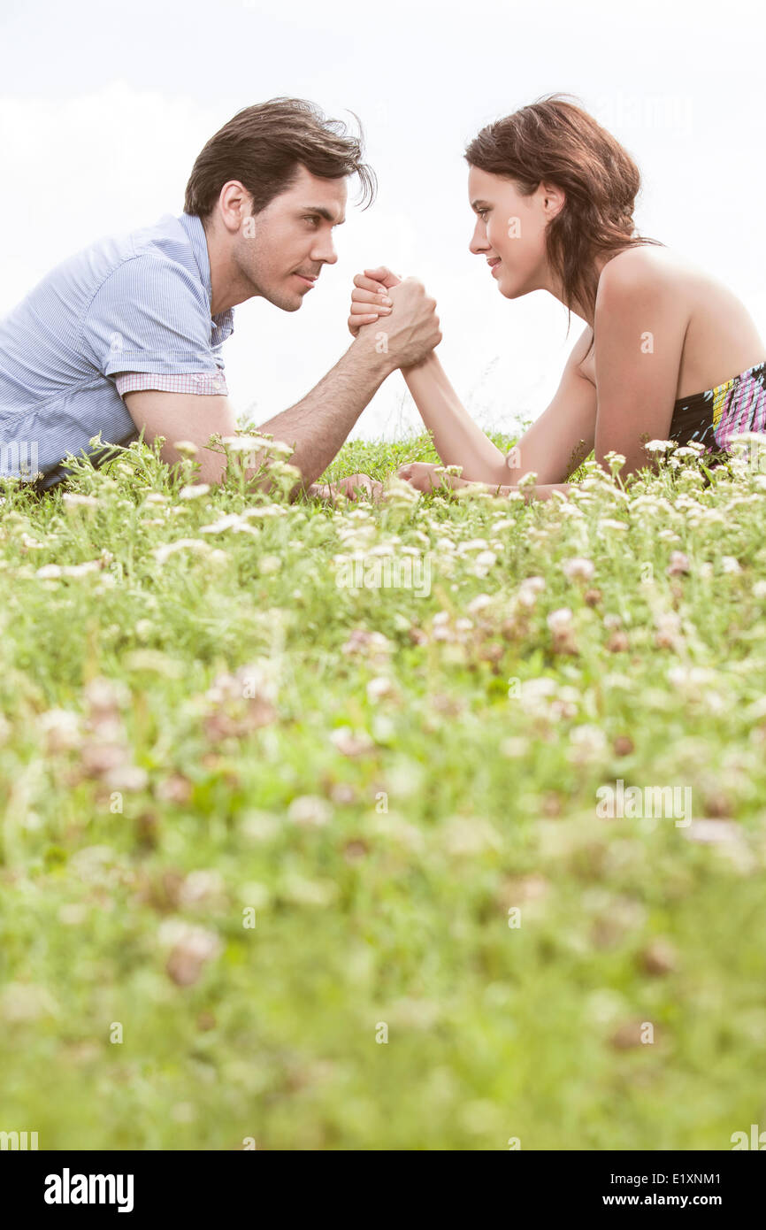 Profile shot of couple arm wrestling while lying on grass against sky - Stock Image