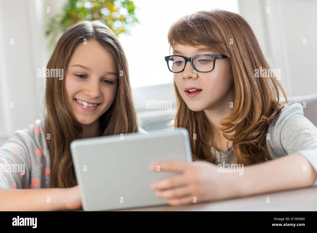 Sisters using digital tablet at table in house - Stock Image