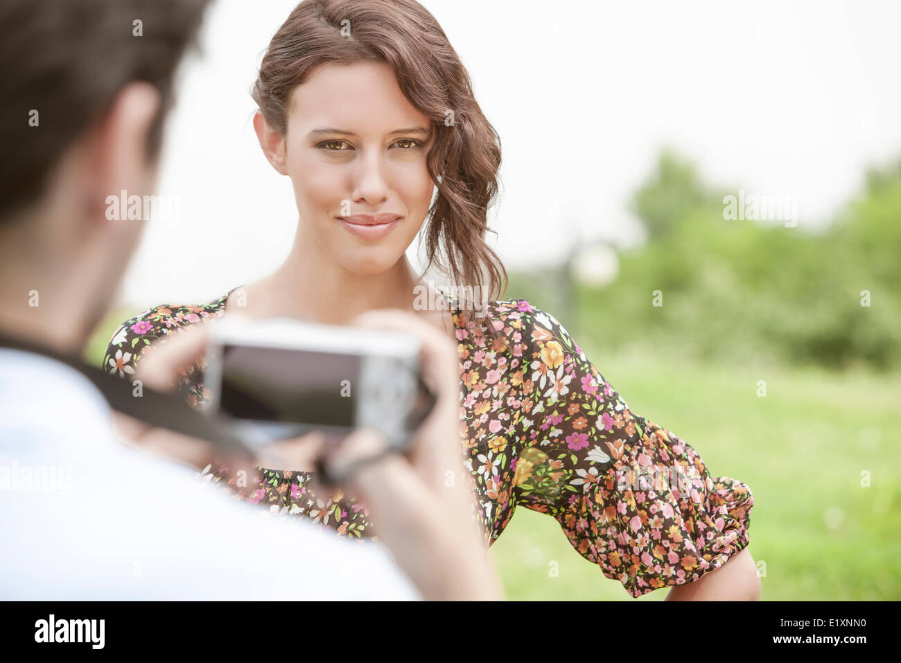 Portrait of confident woman being photographed by man in park - Stock Image