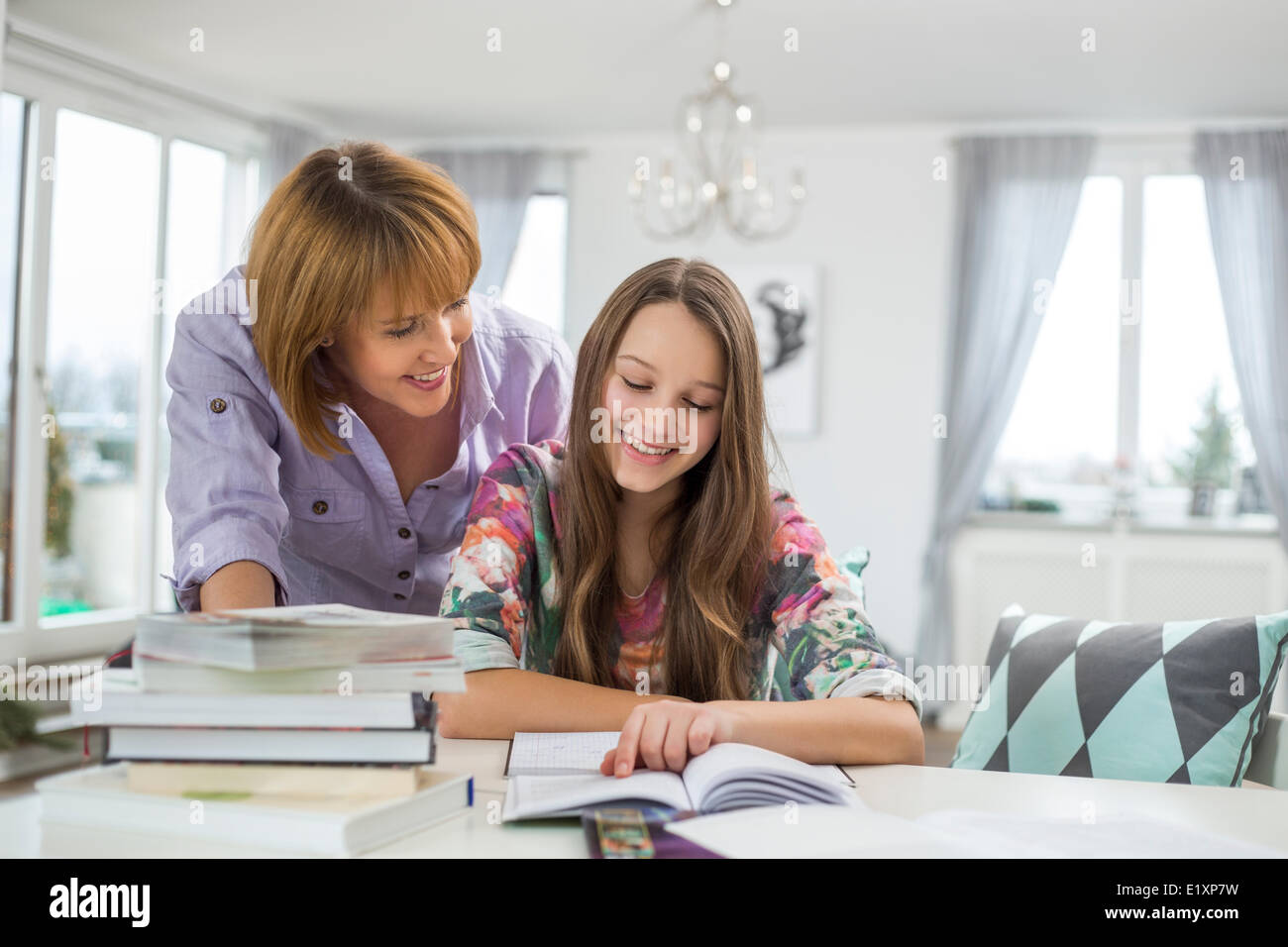 Smiling mother assisting daughter in doing homework at table - Stock Image