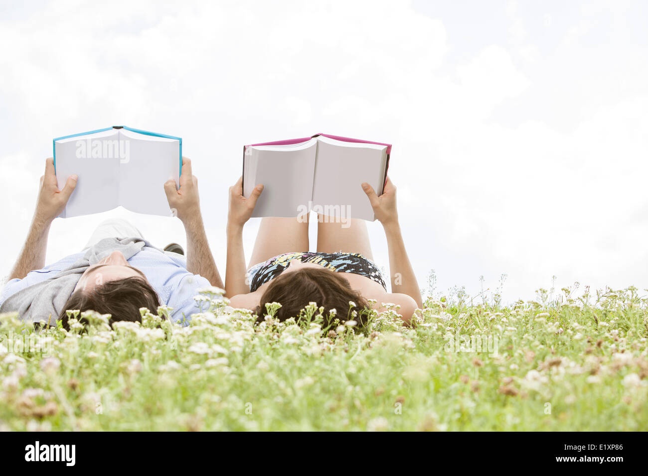 Relaxed young couple reading books while lying on grass against sky - Stock Image