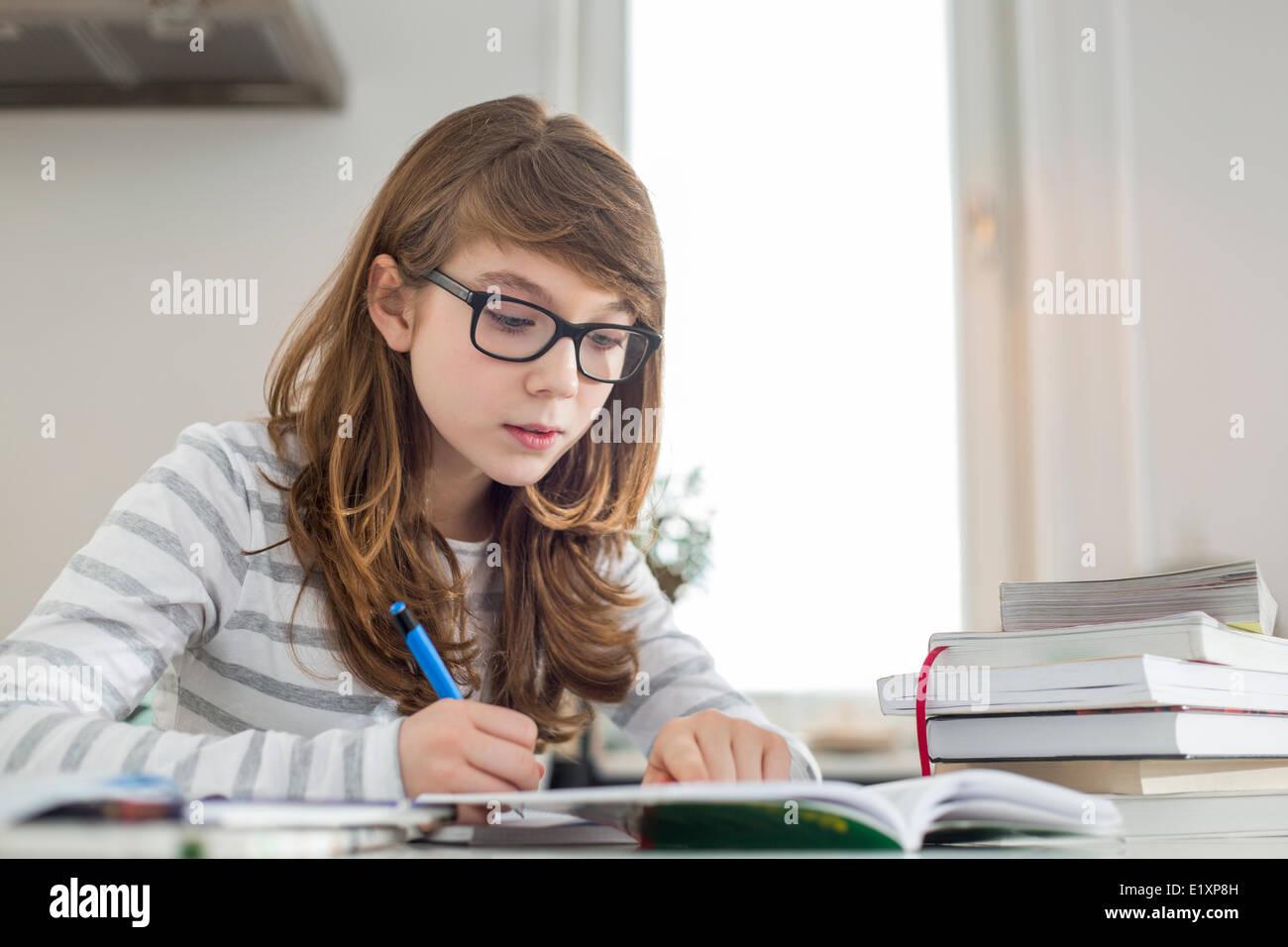 Teenage girl doing homework at table - Stock Image