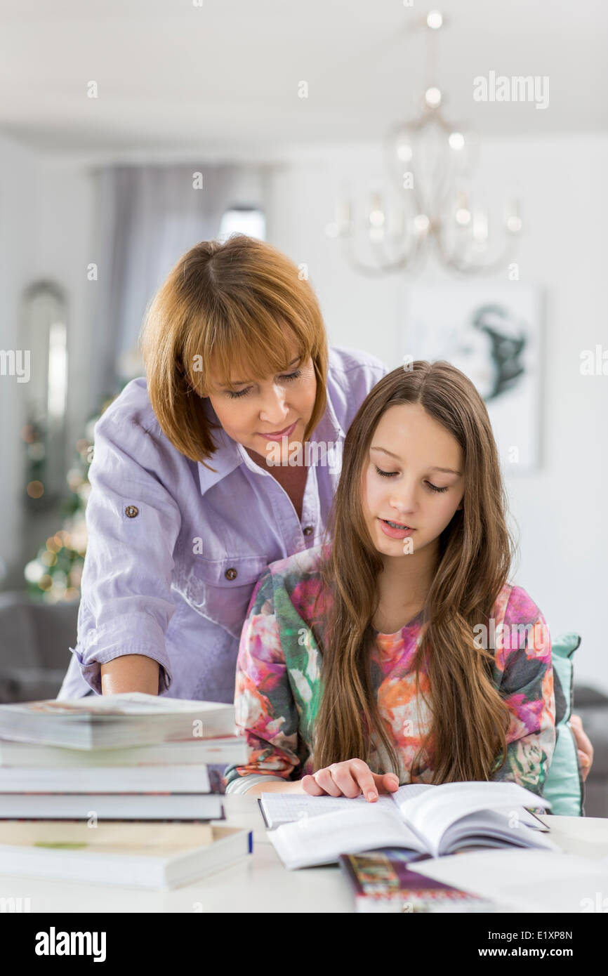 Mother guiding daughter in doing homework at table Stock Photo