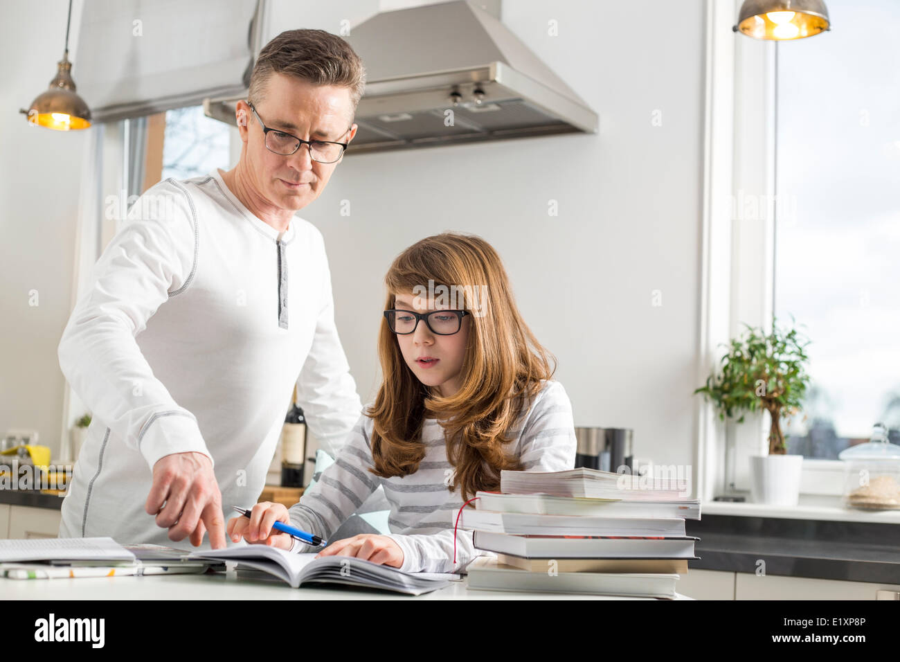 Father guiding daughter in doing homework at table - Stock Image