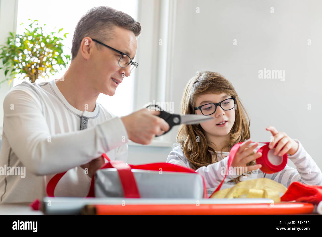 Father and daughter wrapping Christmas presents at home - Stock Image