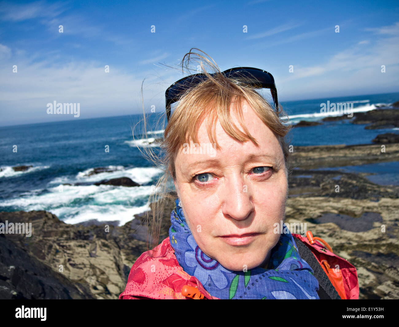 Middle aged woman in front of a seaside landscape. - Stock Image