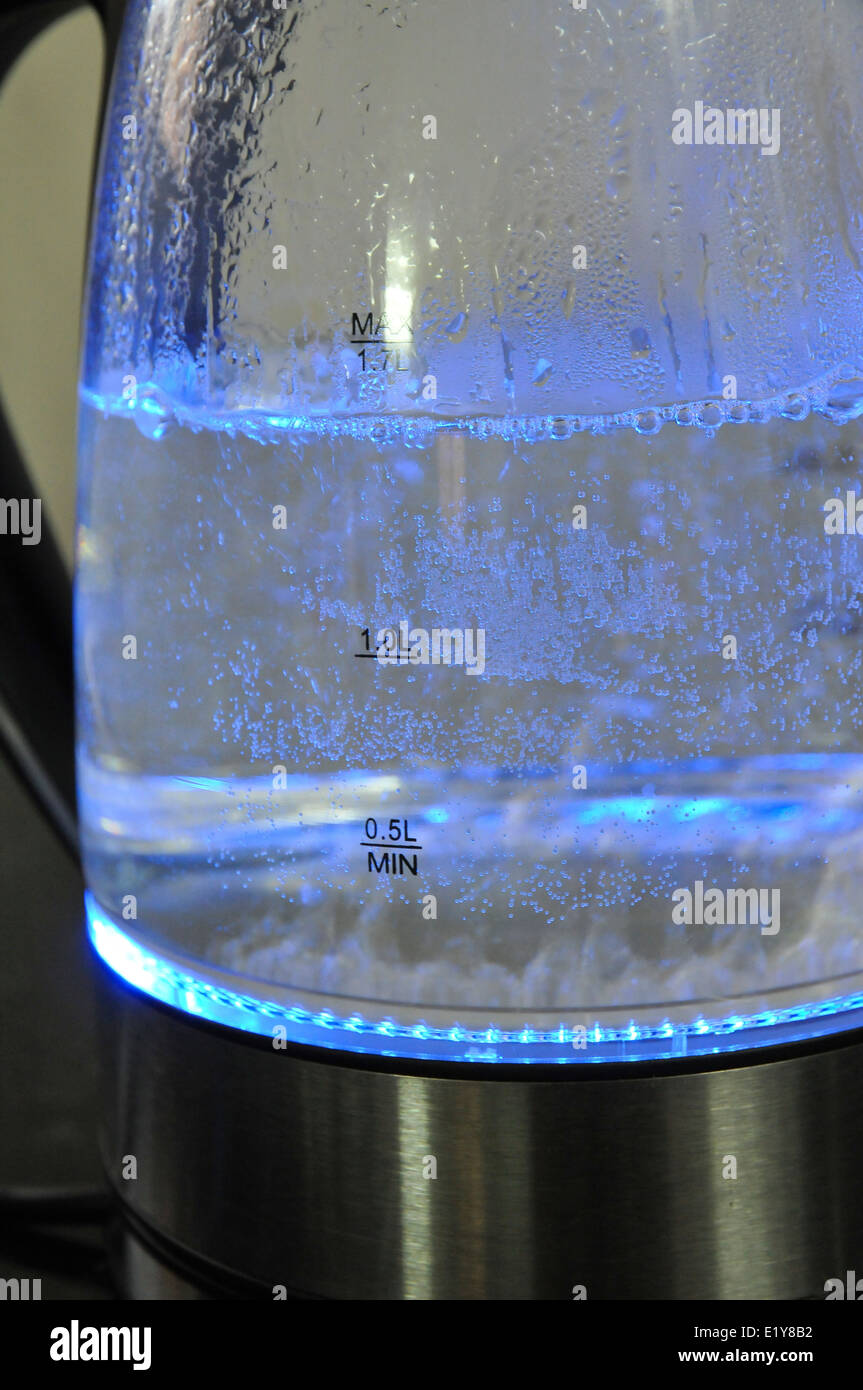 water boiling in a transparent kettle  - Stock Image