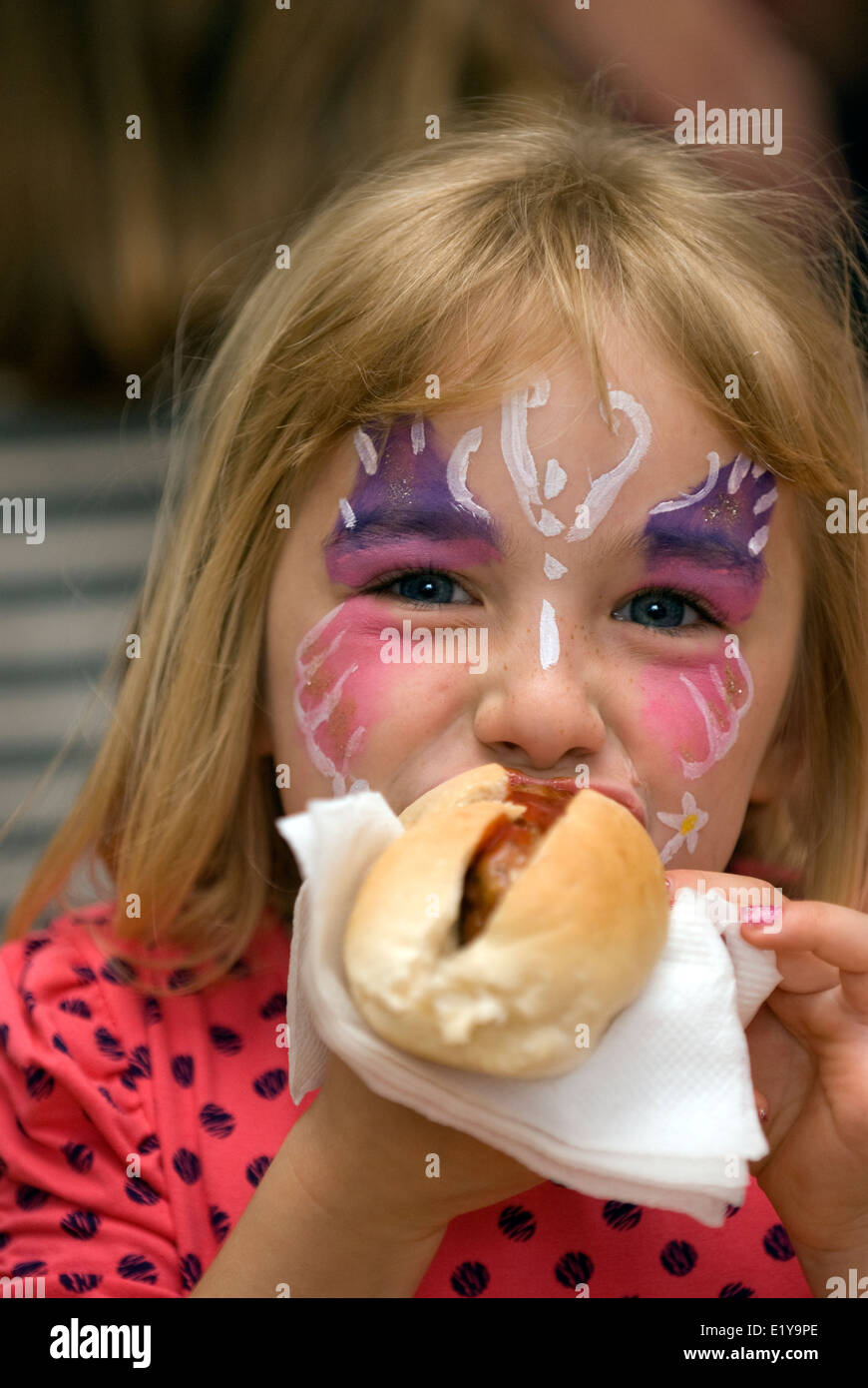 Young girl with her face painted eating a hot dog on her 6th birthday at an infant's school summer fair, Petersfield, - Stock Image