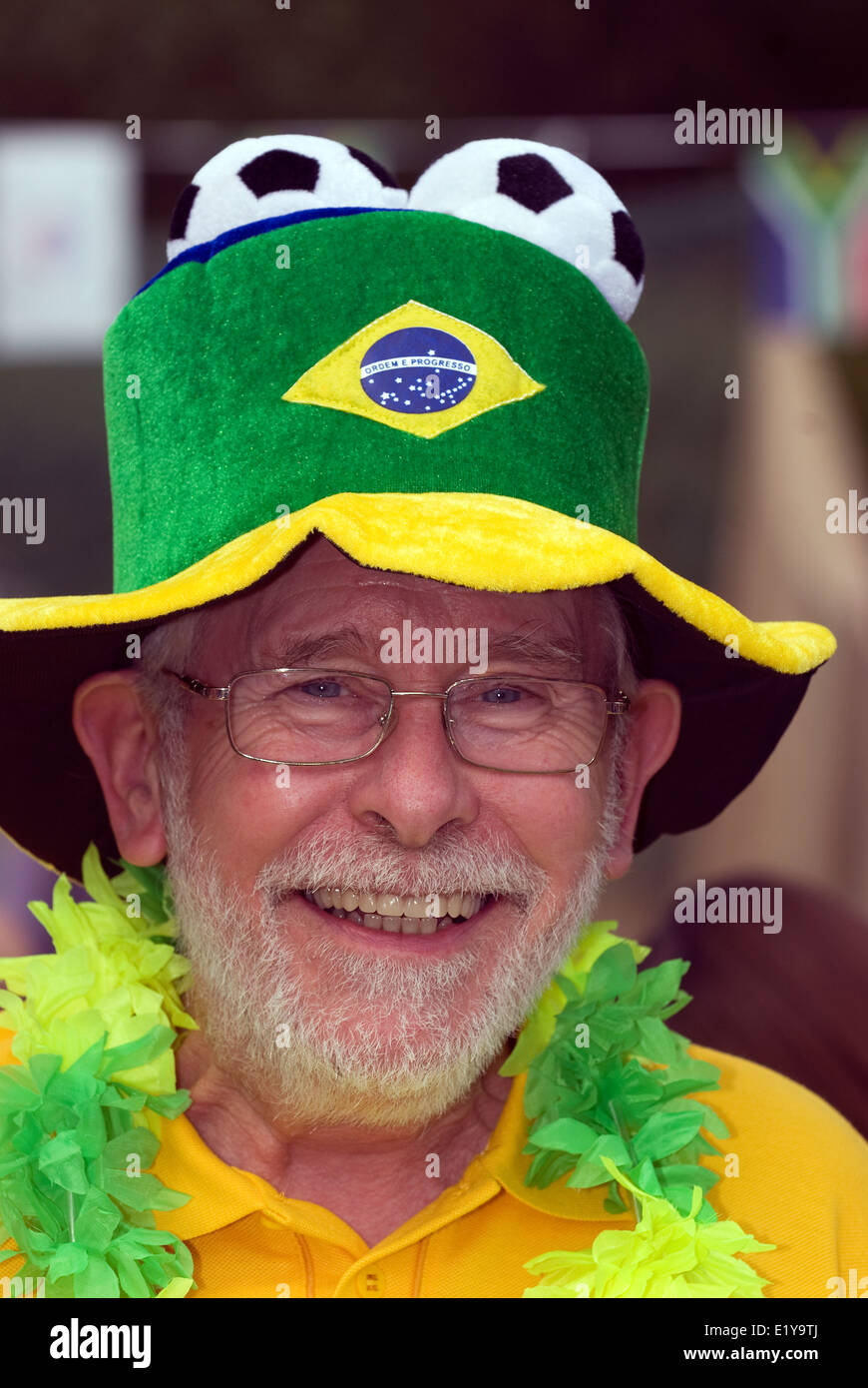 Elderly man at a village summer fair which had a Brazil/World Cup 2014 theme, Dockenfield, UK. - Stock Image