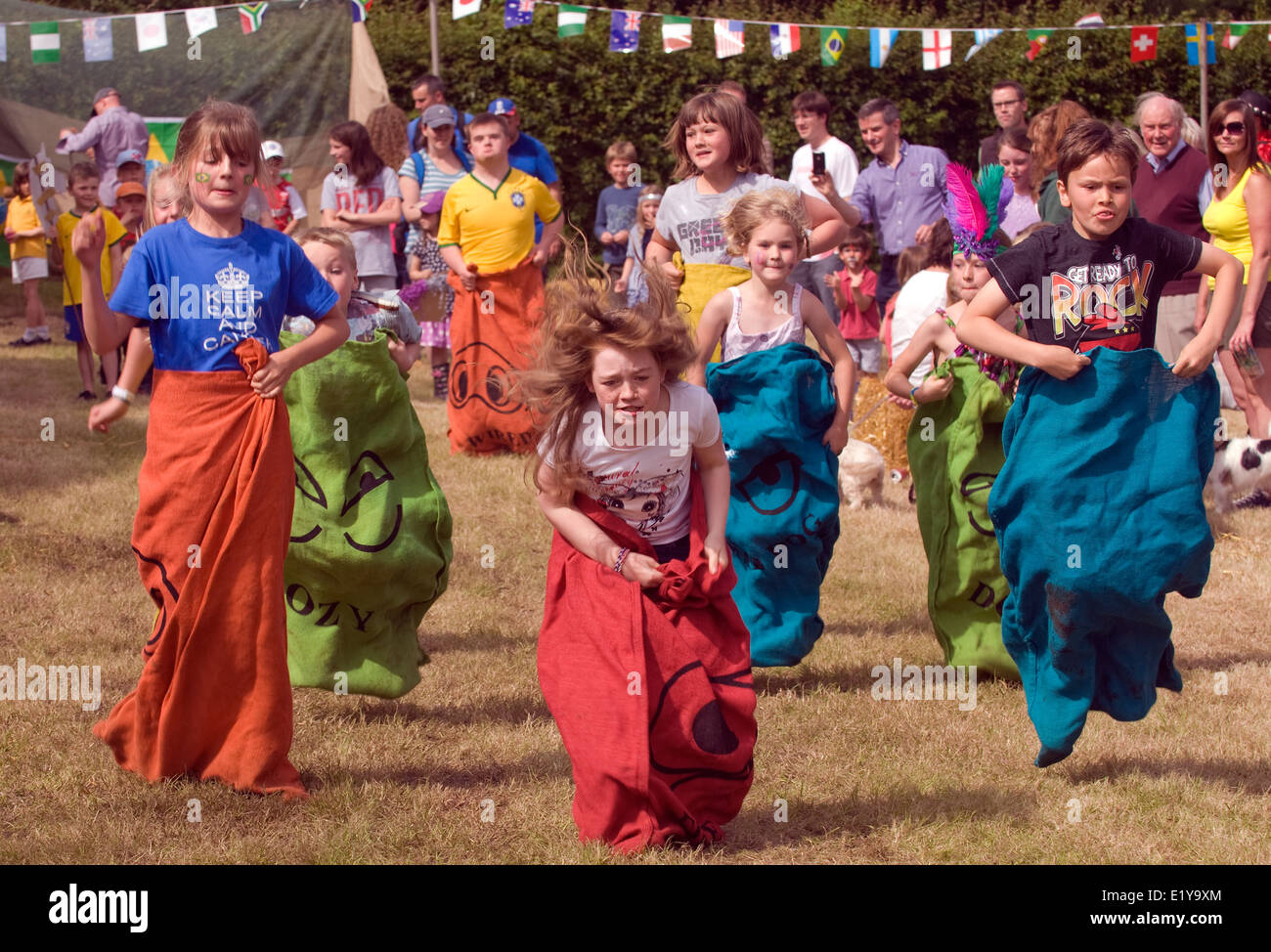 Youngsters competing in a sack race at a village summer fair, Dockenfield, UK. - Stock Image