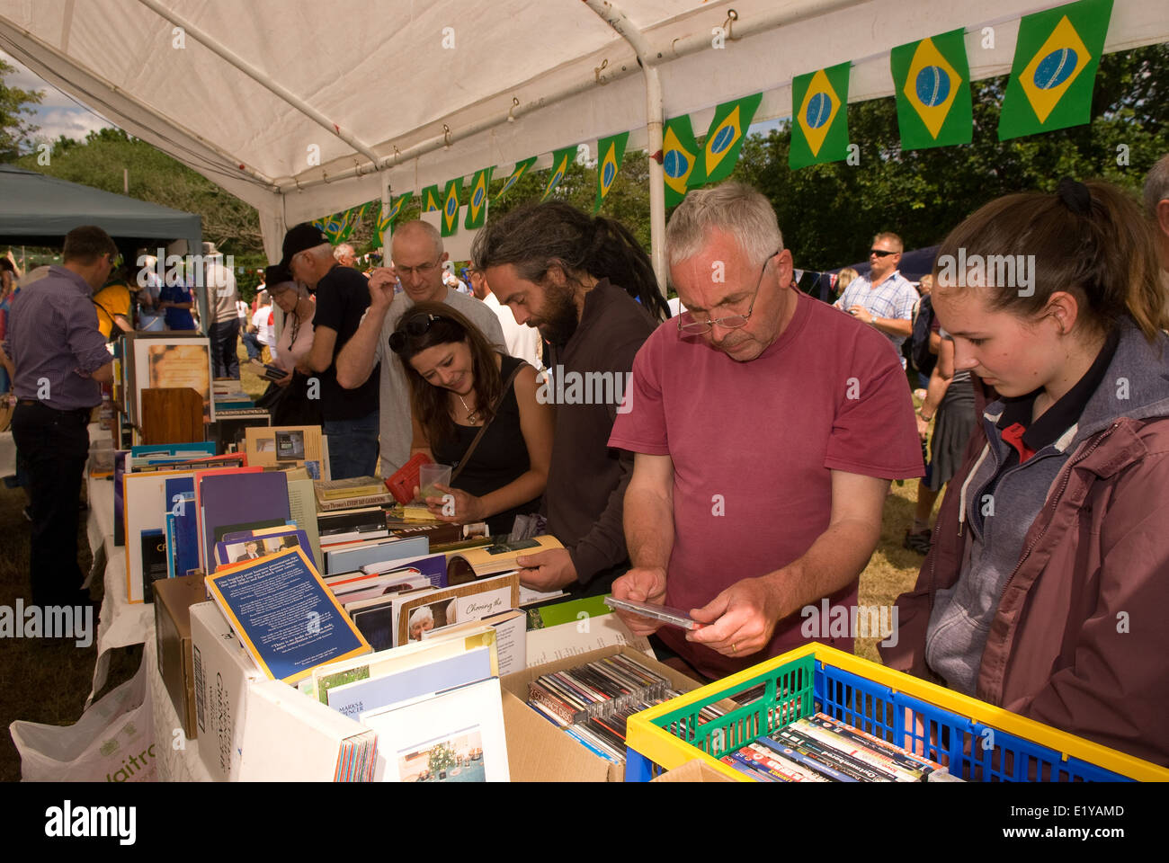 Visitors perusing book stall at a village summer fair which had a Brazil/World Cup 2014 theme, Dockenfield, UK. - Stock Image