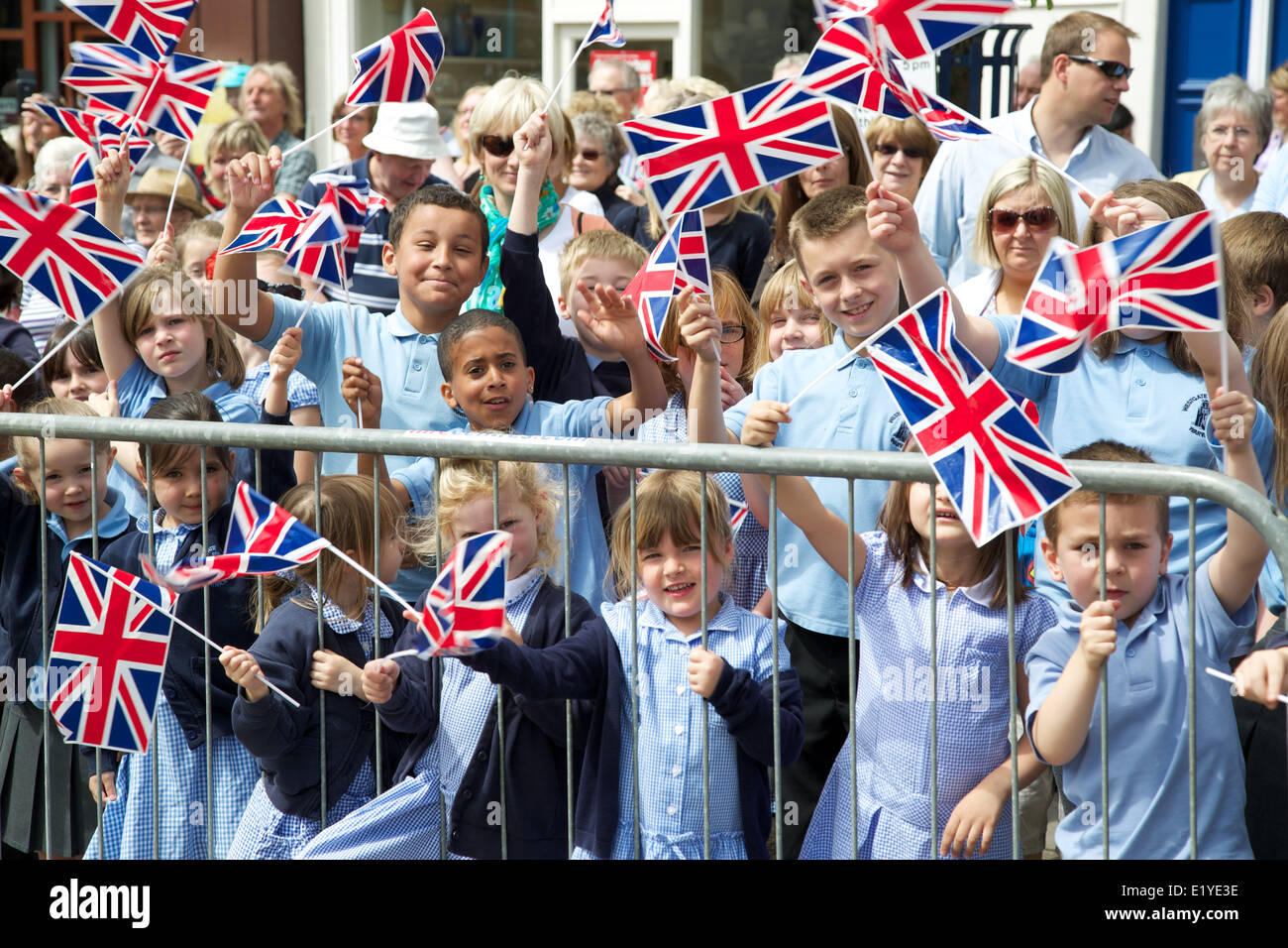 Crowds of schoolchildren line the streets of warwick for a freedom parade by the warwickshire fusilliers waving - Stock Image