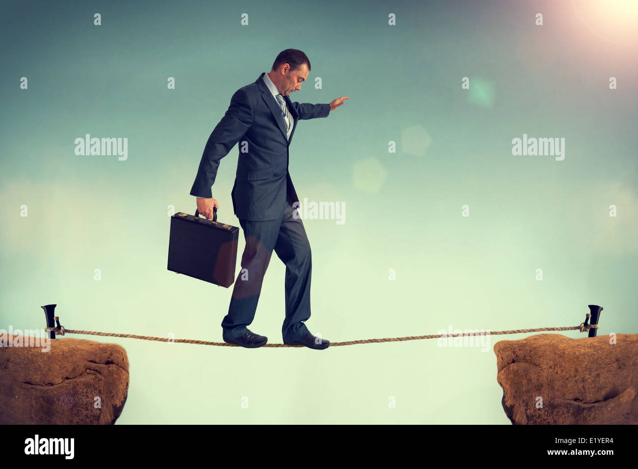 businessman predicament balancing or walking a tightrope or highwire. business concept of challenge, risk, danger, - Stock Image