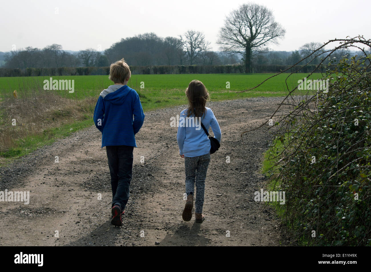 Children walking outdoors in the springtime. Siblings -11 year old boy and 9 year old girl. - Stock Image