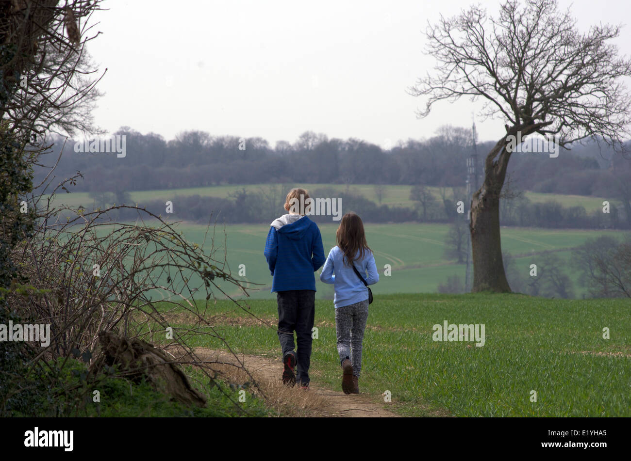 2 children walking outdoors in the springtime. Siblings -11 year old boy and 9 year old girl. - Stock Image