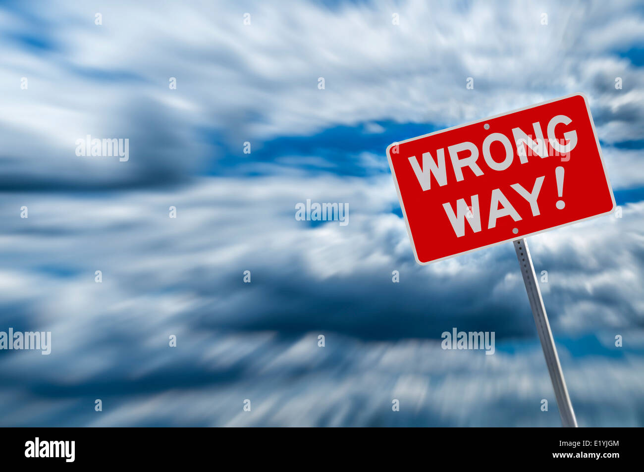 Wrong way warning sign backed by cloudy sky - Stock Image
