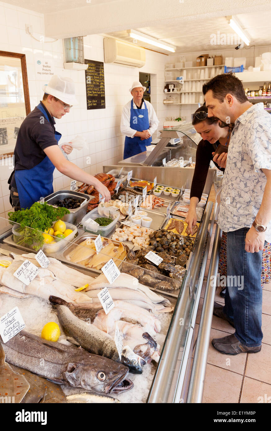 People buying fish in a local fishmonger shop, West Bay, Dorset England UK - Stock Image