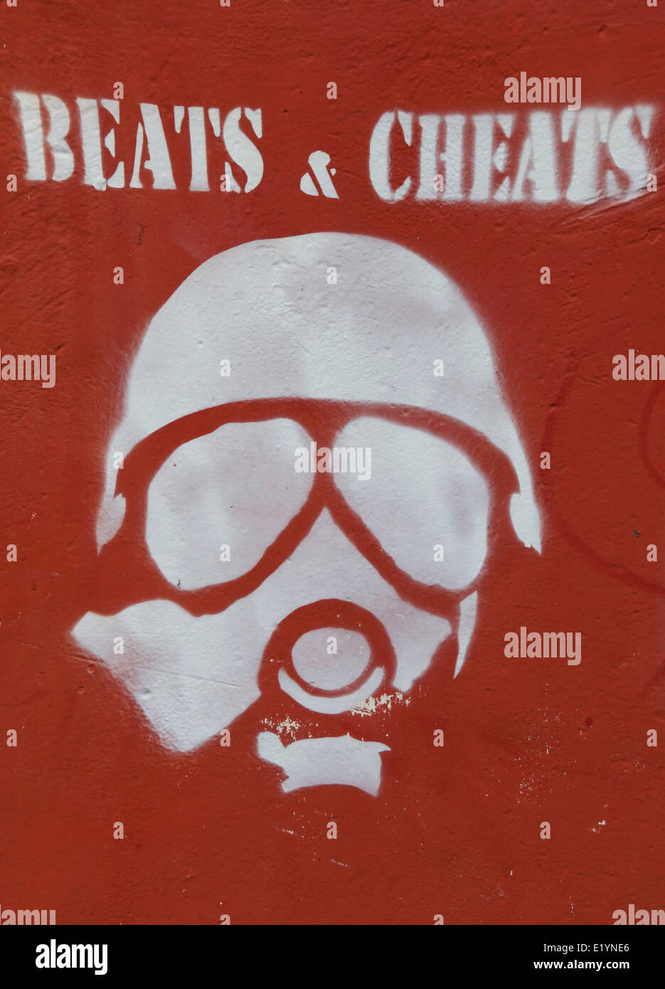 Beats & Cheats red stencil gas mask figure on red hoarding, Islington, Manchester, UK - Stock Image