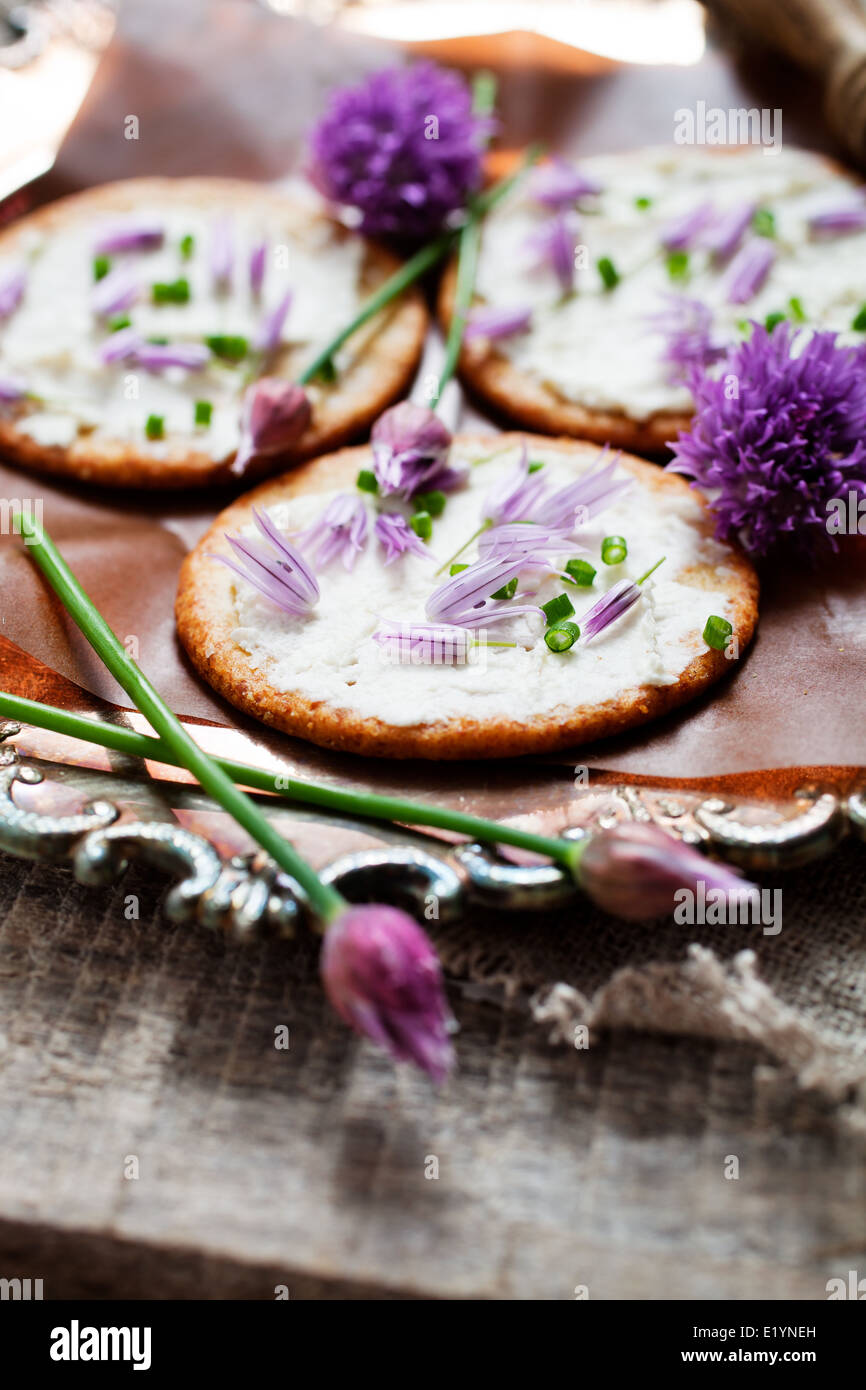 Crackers with fresh chives and cream cheese - Stock Image