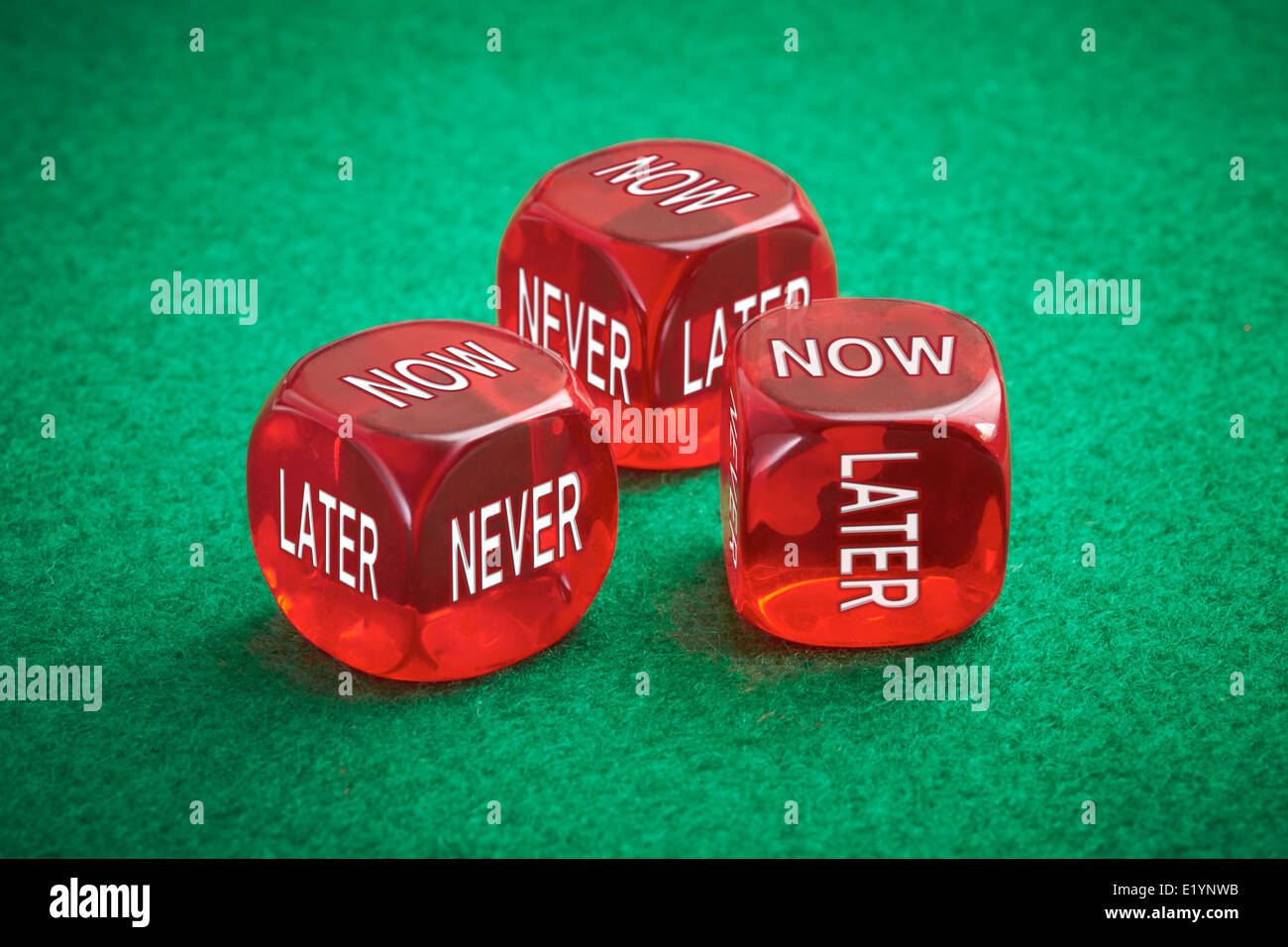 Wasting time concept, three red dice on a green felt background. - Stock Image
